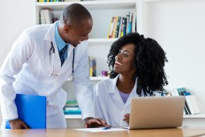 African american chief physician with young female doctor at work at hospital
