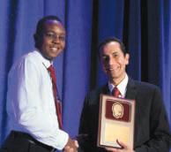 Dr. Edward Kija received a plaque and congratulations as the 2015 Bernard D'Souza Fellowship Awardee from CNS International Affairs Chair, Dr. Jorge Vidaurre.